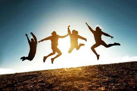 Four silhouettes of friends are jumping together against blue sky and sun